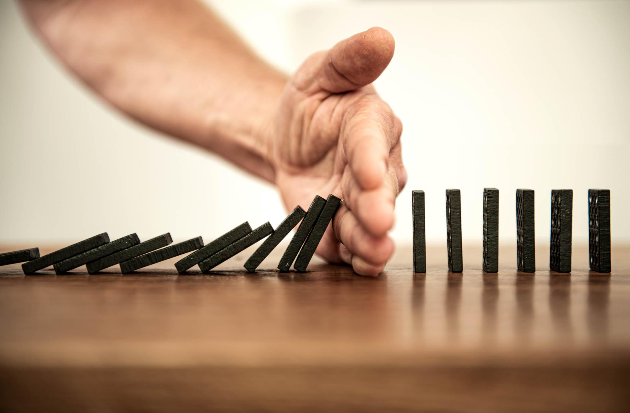 Domino Effekt wird durch eine Hand gestoppt
